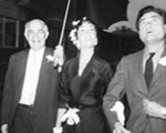 Chancellor Clifford C. Furnas holds umbrella for Elizabeth Taylor and her husband, Mike Todd